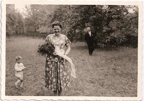 Schwarz-Weiß-Aufnahme: Meine Großmutter in einem Kleid auf einer Wiese, im Hintergrund mein Großvater.