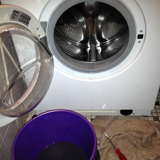 Kaputte Bauknecht-Waschmaschine mit Wassereimer davor