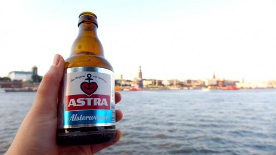 Eine Flasche Astra Alsterwasser vor der Kulisse der Elbe mit Hamburger Hafen