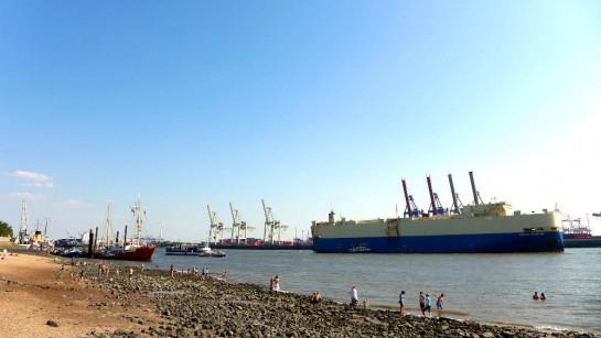 Elbstrand. Leute baden. Containerschiff fährt vorbei.