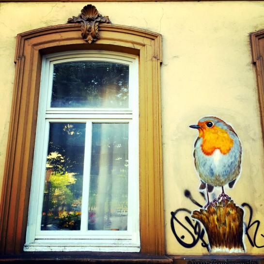 Altbaufenster mit einem auf die Fassade gemalten Rotkehlchen.