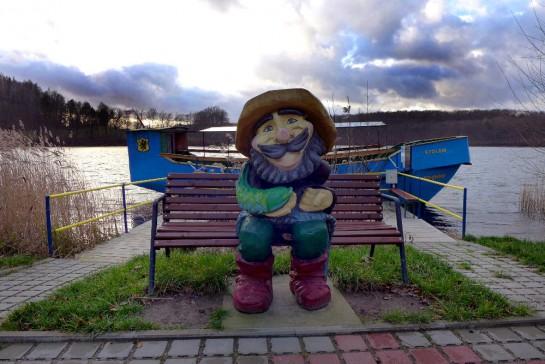 Ostrzyce, am Seeufer: Geschnitzte Fischerfigur mit Boot im Hintergrund