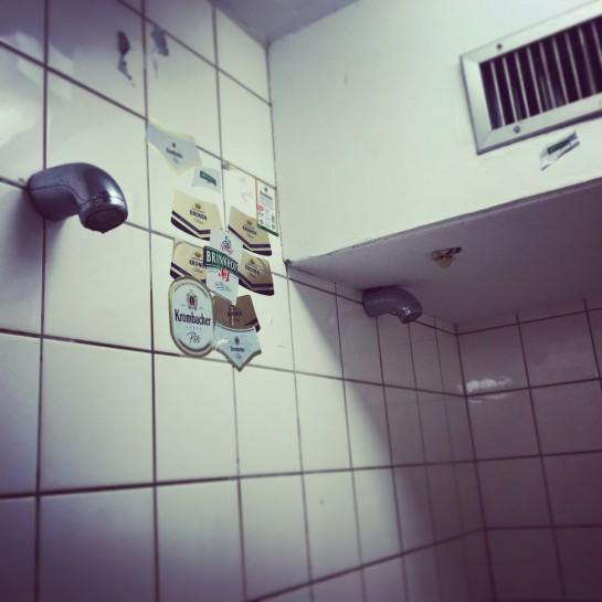 Dusche in der Turnhalle, mit Bieretiketten an der Wand