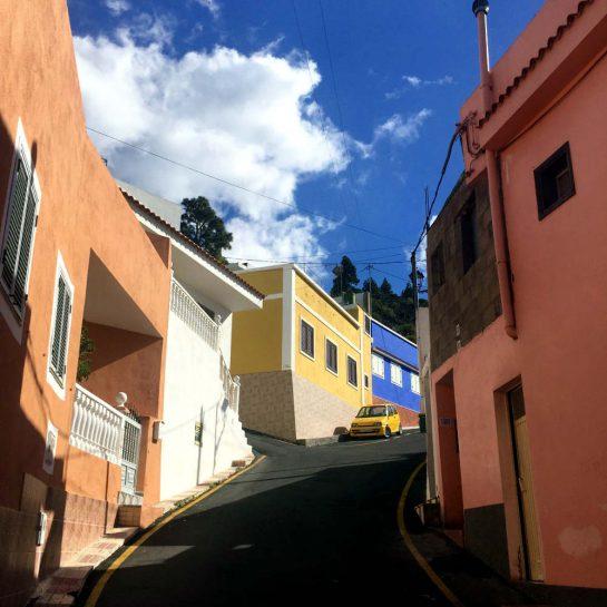 Steil ansteigende Dorfstraße zwischen Häusern