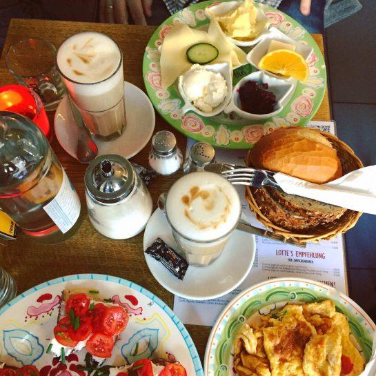 Frühstückstisch mit Brötchenkorb, Rührei und allerlei leckerem Zeug