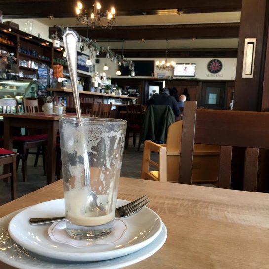 Gaststube mit leerem Kaffeeglas, in der Fernse ein Fernseher mit Skispringen