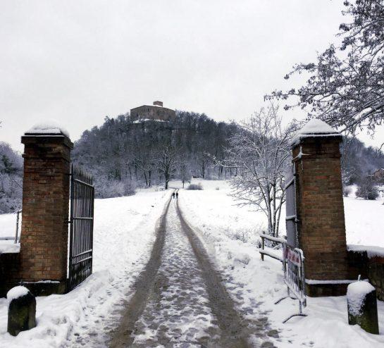 Castello di Bianello: Eingangstor, im Hintergrund die Burg auf einem Berg