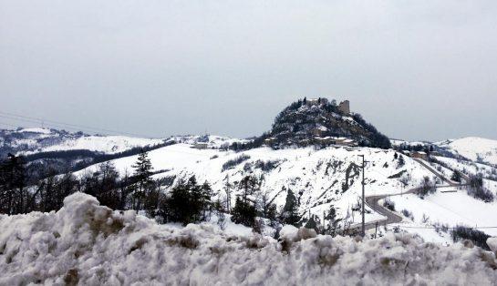 Blick über die Schneeberge an der Straße hinweg auf den Hügel mit der Canossa-Ruine