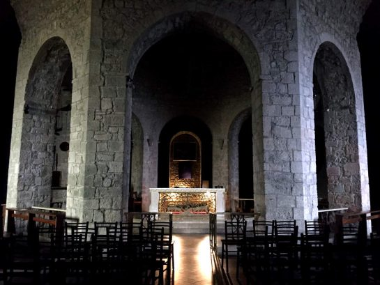 Krypta: Gemauerte Bögen mit wenig Licht, dazwischen ein Sarkophag