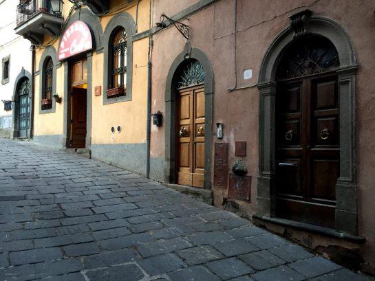 Pizzeria an steile Straße mit geöffneter Tür