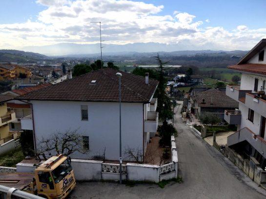 Balkonaussicht in die Berge, unten steht ein Abschleppwagen