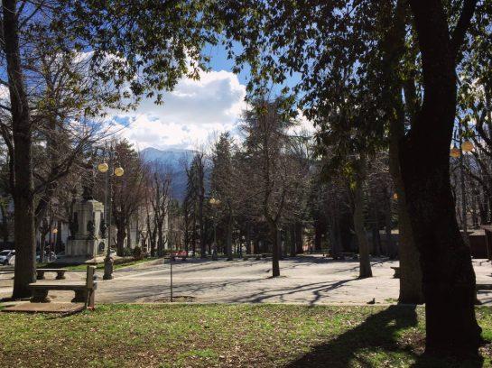 Park in L'Aquila, im Hintergrund ein schneebedeckter Gipfel