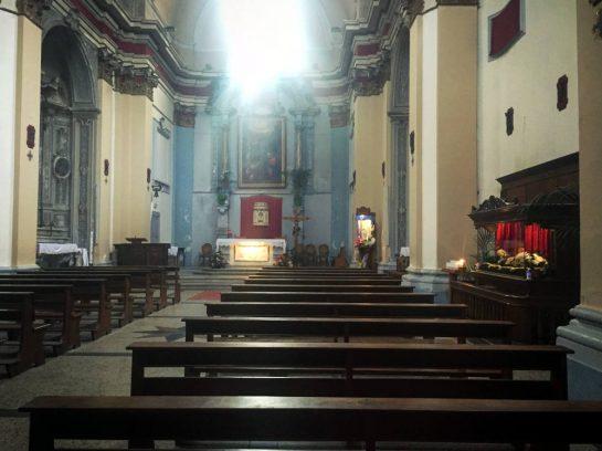 Kirche, rechts ein Glaskasten mit einer liegenden Figur