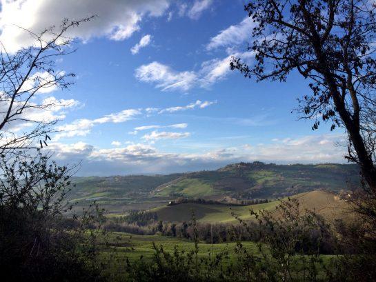 Via Montevarmine: Blick in die hügelige Landschaft mit Sonne und Schäfchenwolken