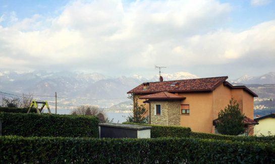 Ausblick von der Terrasse in Bianica: Ein orangenes Haus, dahinter Berge und See