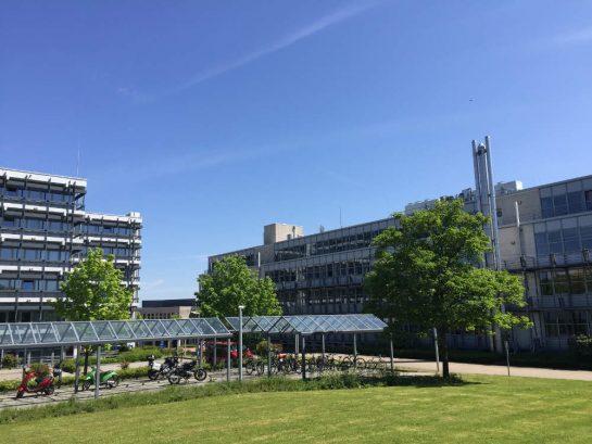 Fernuni Hagen: Blick über eine Wiese auf ein Hochschulgebäude bei Sonne