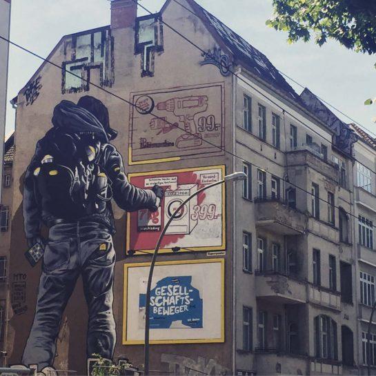 Berlin: Haushohes Graffiti einer Person von hinten, die eine Werbeanzeige an die Hauswand sprüht