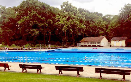 Freibad mit zwei Schwimmerbahnen, Bänken und Wiese