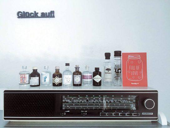 """Kleine Flaschen Gin auf einem alten Radio, darüber Schriftzug """"Glück auf!"""""""