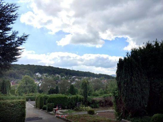 Friedhofsaussicht: Berg runter mit Grräbern, dahinter berg rauf mit Häusern