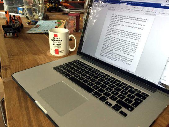 MacBook auf Esstusch mit Kram drumherum