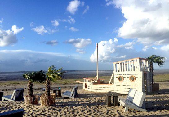 Strand mit wehenden Palmen und Holzschiff