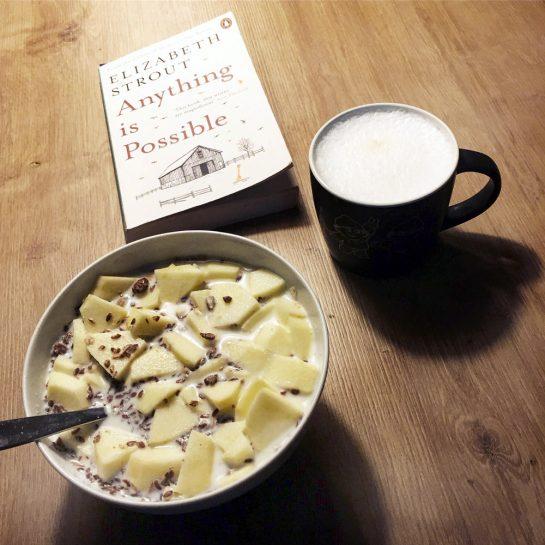 Müslischale, Kaffebecher und das Buch von Elizabeth Strout