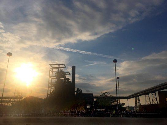 Modus Mio: Menschenschlange vor Industriekultur und untergehender Sonne