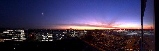 Aussicht über Flughafen und angrenzende Geschäftshäuser im Abendrot