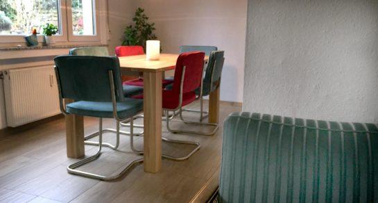 Tisch mit vier petrolfarbenen und zwei roten Stühlen, im Vordergrund die Kante eines Sofas