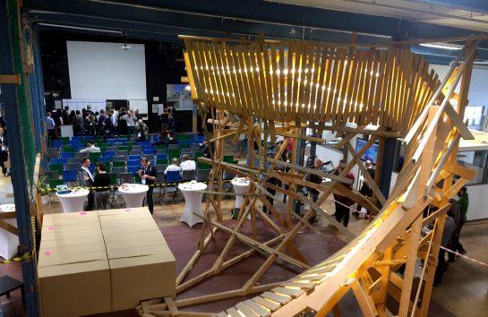 Agile Barcamp: Im Hintergrund Stühle und Menschen, im Vordergrund eine große Kunstinstallation aus Holz