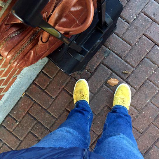 Von oben auf die Füße fotografiert: Koffer, Laptoptasche, Jeans und gelbe Sneakers