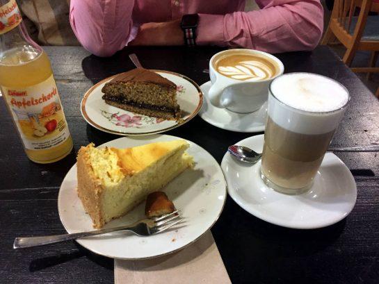 Zwei Teller mit Kuchen, zwei Kaffee, eine Apfelschorle. Im Hintergrund die Arme eines Mannes im rosa Hemd.
