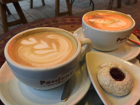 Zwei Tassen Milchkaffee mit einem Keks