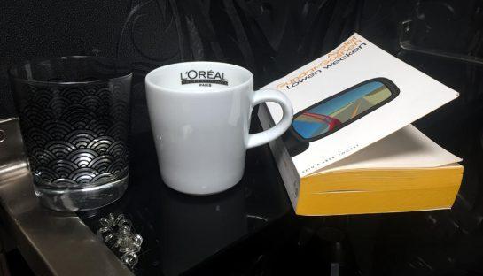 Glas Wasser, Tasse Kaffee, Buch vor schwarzer Tapete