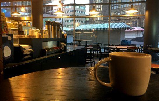Blick über einen Kaffeebecher in ein Café, draußen Wochenmarkt
