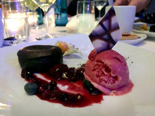 Schnieker Nachtisch: Schokoküchlein mit Eissorbet aus Waldbeeren, einer Soße und einem Schokoplättchen im Eis