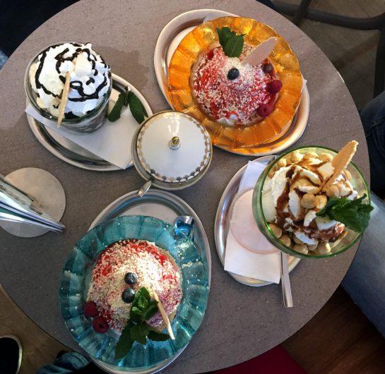 Vier große Eisbecher auf einem Tisch, fotografiert von oben.