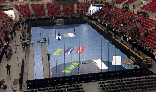 Handballfeld von oben, Männer rollen das Spielfeld auf.