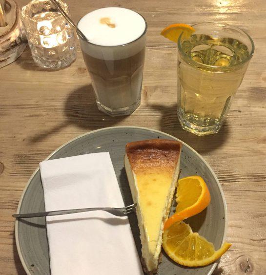 Käsekuchen, Latte Macchiato, Birnenschorle auf einem Holztisch.