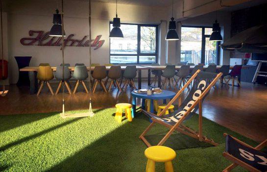 Coworking-Space mit Kunstrasen, Liegestuhl und Schaikel, im Hintergrund Tischreihe mit bunten Stühlen