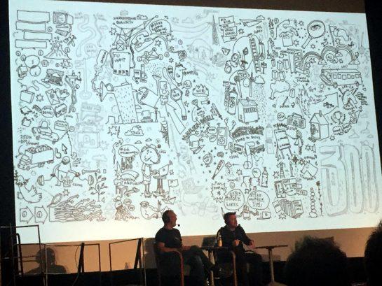 """Ein großes Bild, dessen einzelne Zeichnungen die Buchstaben """"LNP"""" bilden. Davor zwei Männer auf der Bühne."""