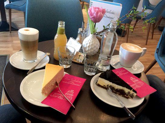 Zwei Teller mit Kuchen (Kästekuchen und Oreo Cheesecake), dazu Kaffee. Eine Vase mit einer rosa Blumeim Hintergrund.