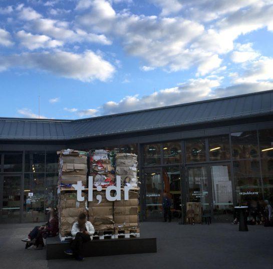 """Ein Papierstapel im Hof der """"Station Berlin"""", den dem die Zeichen """"tl;dr"""" angebracht sind. Davor sitzt ein Mann. Der Himmel ist blau mit weißen Wolken."""