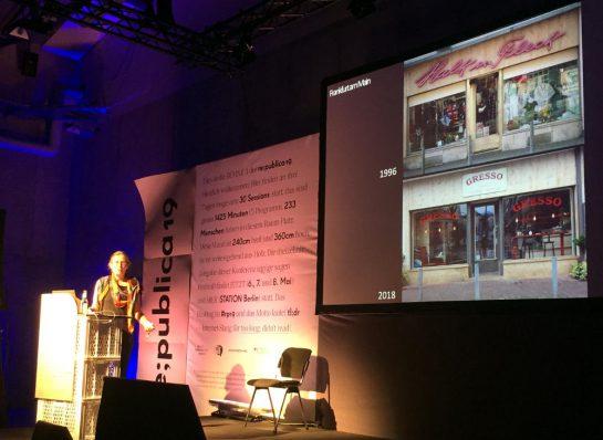 Kirsten Kötter auf der Bühne der re:publica, neben ihr die Leinwand mit zwei Bildern eines Einzelhandelsgeschäfts: 1998 ein Fachhandel, 2018 ein Imbiss.