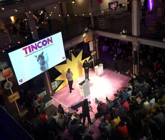 Blick aus der Vogelperspektive auf eine Session der Tincon. Menschen, Lichterketten.
