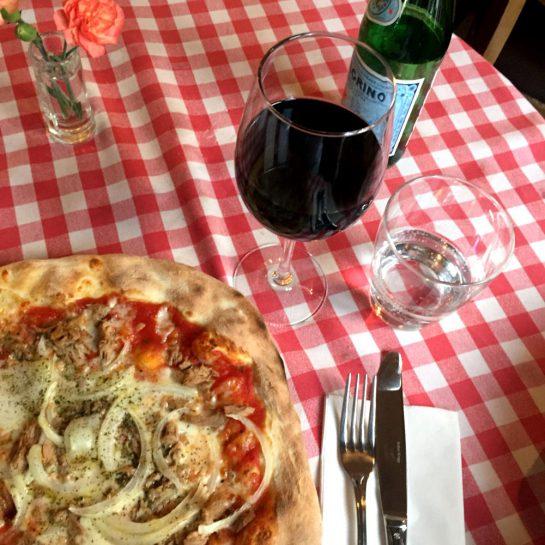 Pizza Thunfisch, ein Glas Rotwein und ein Glas Wasser auf rot-weiß-karierter Tischdecke