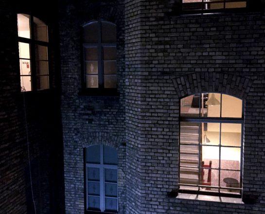 Dunkel. Blick auf ein Backsteingebäude mit erleuchteten Industriefenstern. Darin ein Treppenhaus.