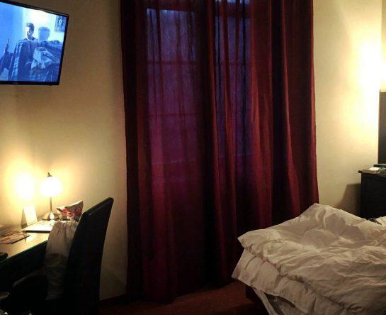 Hotelzimmer. Auf 3 Uhr das Ende eines Bettes mit weißem Federbett. Auf 12 Uhr geschlossene, rote Vorhänge. Auf 10 Uhr ein dunkler Schreibtisch, darüber  ein Fernseher.
