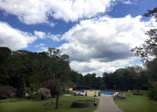 Blick aus der Ferne aufs Freibadschwimmbecken. Blauer Himmel mit Schäfchenwolken.